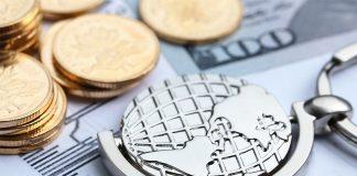 Monedas y billetes con llavero de mundo