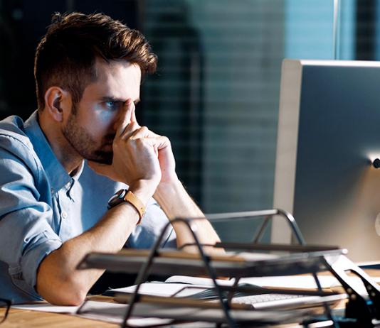 Hombre frustrado frente a computadora